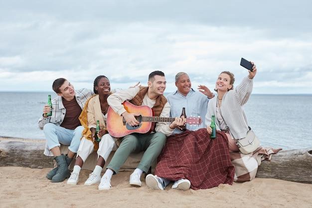 Jonge vrienden nemen selfie op strandfeest