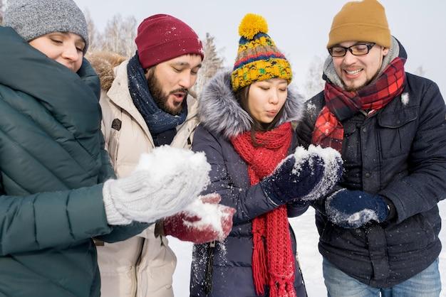 Jonge vrienden spelen met sneeuw