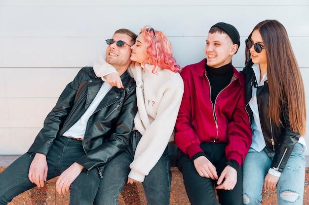 Jonge vrienden zittend op een bankje en plezier maken