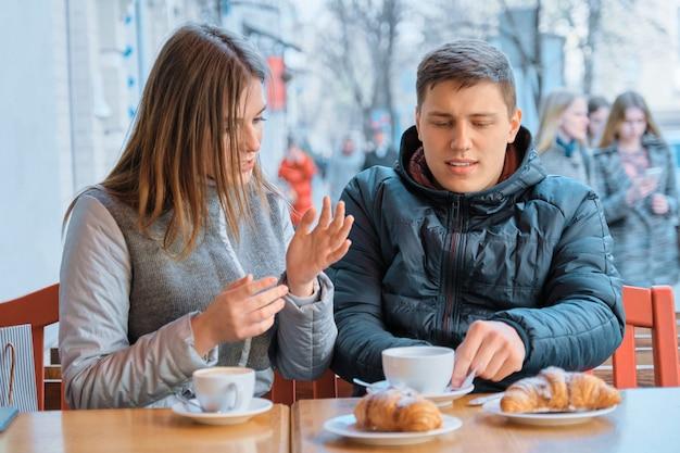 Jonge vriendenman en vrouw die in openluchtkoffie spreken