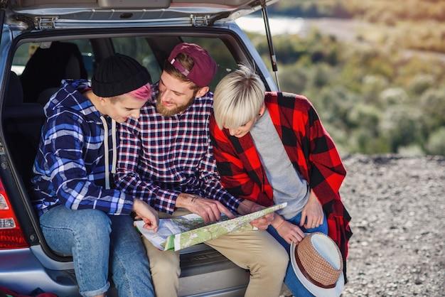 Jonge vriendenreizigers die op boomstam van auto zitten en de document kaart bekijken.