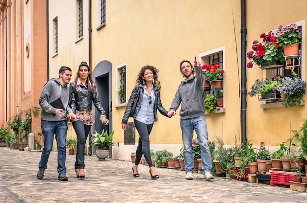 Jonge vriendentoeristen die in oude stad bij vrije gangtocht lopen