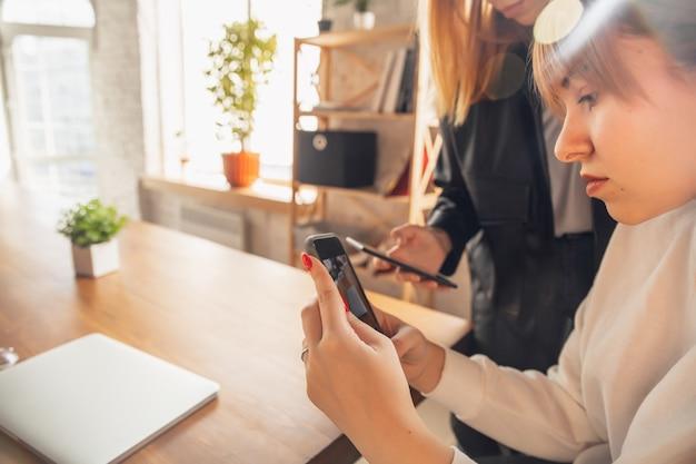 Jonge vriendenvrouwen die gadgets gebruiken