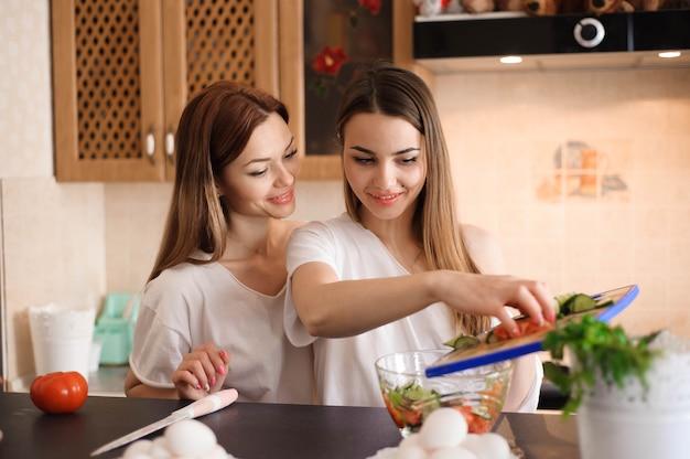 Jonge vriendinnen hakken groenten met tweeling in een huiskeuken.