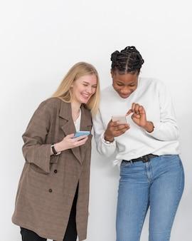 Jonge vriendinnen kijken naar mobiel