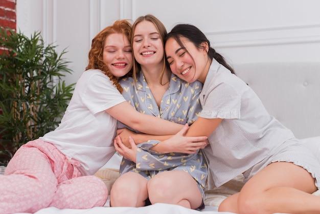 Jonge vriendinnen knuffelen in bed