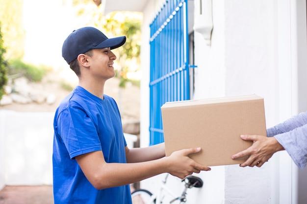 Jonge vriendschappelijke leveringsmens die kartondoos thuis levert