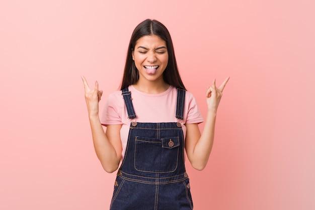 Jonge vrij arabische vrouw die een jeansboomgaard draagt die rotsgebaar met vingers toont