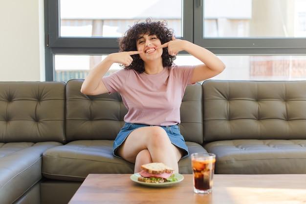 Jonge vrij arabische vrouw die een sandwich zittend op een bank thuis heeft