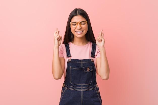 Jonge vrij arabische vrouw die jeansslingerbroek dragen die vingers kruisen voor het hebben van geluk