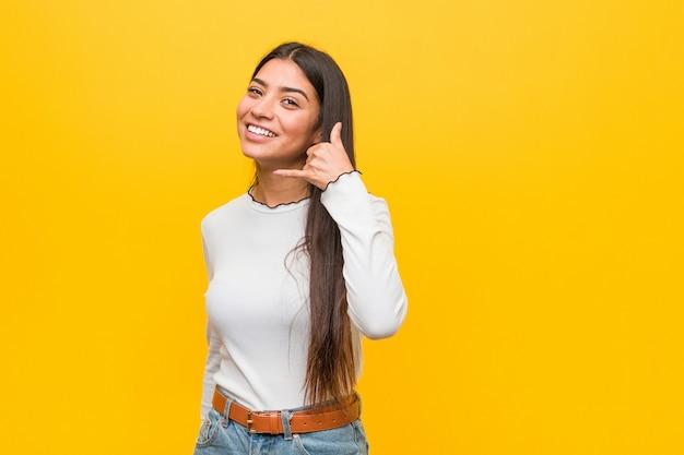 Jonge vrij arabische vrouw tegen een geel die een mobiel telefoongesprekgebaar met vingers tonen.