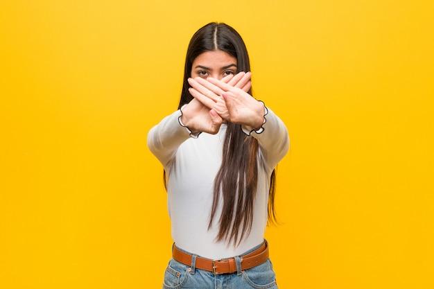 Jonge vrij arabische vrouw tegen een geel die een ontkenningsgebaar doet