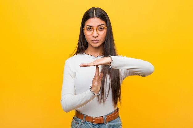 Jonge vrij arabische vrouw tegen geel die een time-outgebaar tonen.