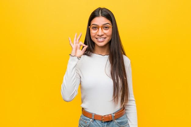 Jonge vrij arabische vrouw tegen geel vrolijk en zeker tonend ok gebaar.