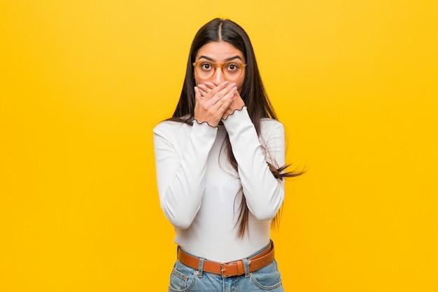 Jonge vrij arabische vrouw tegen gele geschokte bedekkende mond met handen.