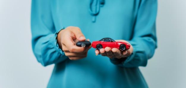 Jonge vrij aziatische de autosleutel van de vrouwenholding en autostuk speelgoed terwijl status in studioschot.