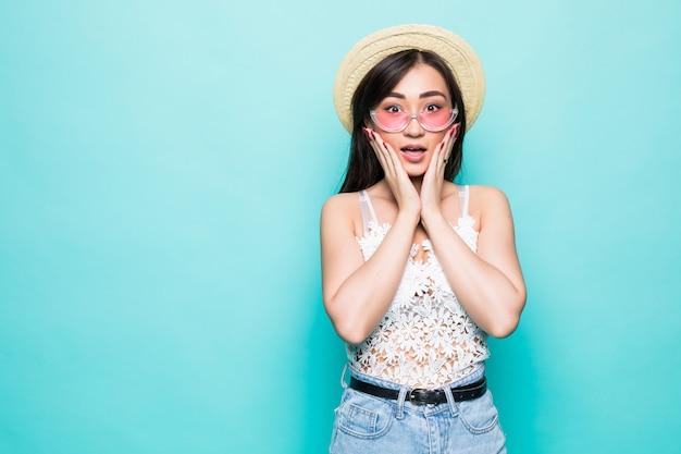 Jonge vrij aziatische die vrouw met zonnebril wordt verrast op groene muur wordt geïsoleerd