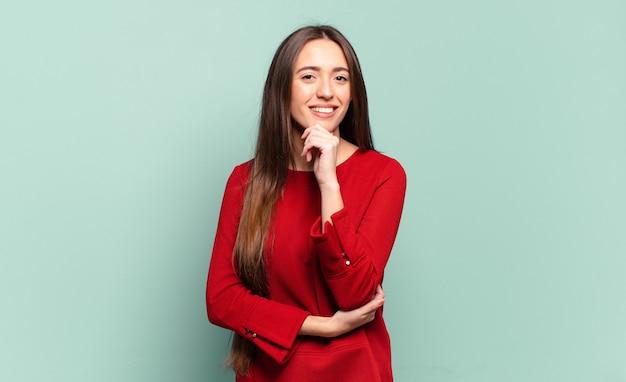 Jonge, vrij casual vrouw die er gelukkig uitziet en glimlacht met de hand op de kin, zich afvraagt of een vraag stelt, opties vergelijkt