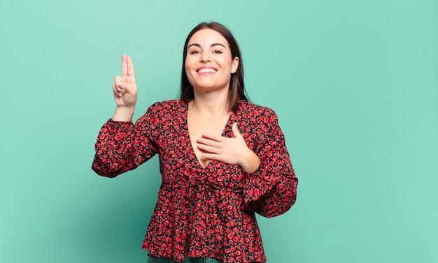 Jonge, vrij casual vrouw die er gelukkig, zelfverzekerd en betrouwbaar uitziet, glimlacht en een overwinningsteken toont, met een positieve houding