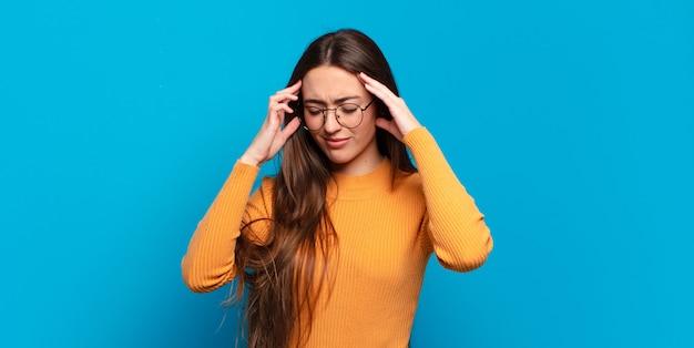 Jonge, vrij casual vrouw die er gestrest en gefrustreerd uitziet, onder druk werkt met hoofdpijn en last heeft van problemen