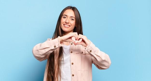 Jonge, vrij casual vrouw die lacht en zich gelukkig, schattig, romantisch en verliefd voelt, hartvorm maakt met beide handen