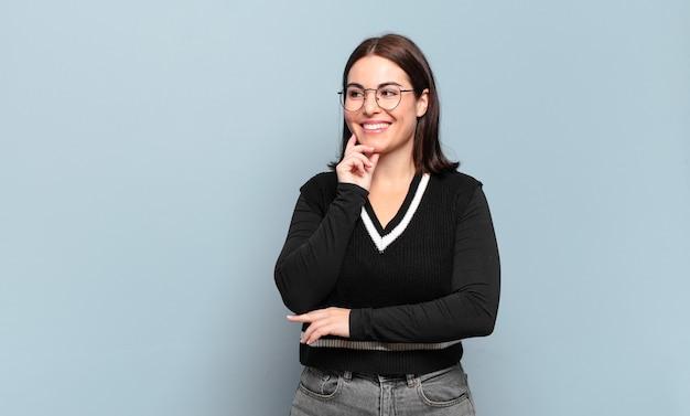 Jonge, vrij casual vrouw die lacht met een gelukkige, zelfverzekerde uitdrukking met de hand op de kin, zich afvragend en opzij kijkend