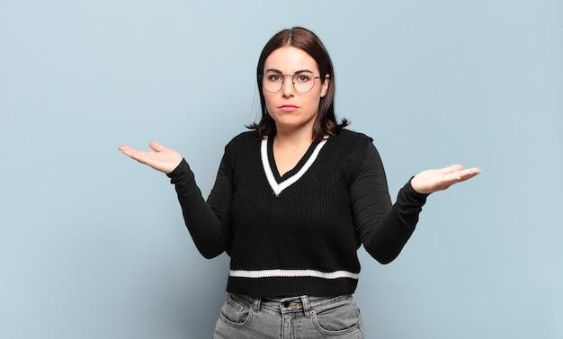 Jonge, vrij casual vrouw die verbaasd, verward en gestrest kijkt, zich afvraagt tussen verschillende opties, zich onzeker voelt
