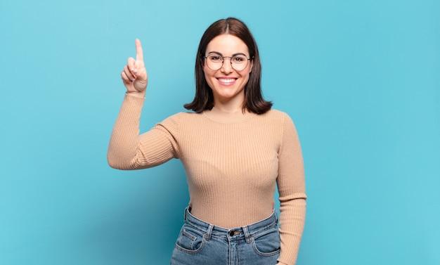 Jonge, vrij casual vrouw die vrolijk en gelukkig lacht, met één hand naar boven gericht om ruimte te kopiëren