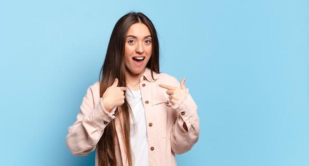 Jonge, vrij casual vrouw die zich blij, verrast en trots voelt en naar zichzelf wijst met een opgewonden, verbaasde blik