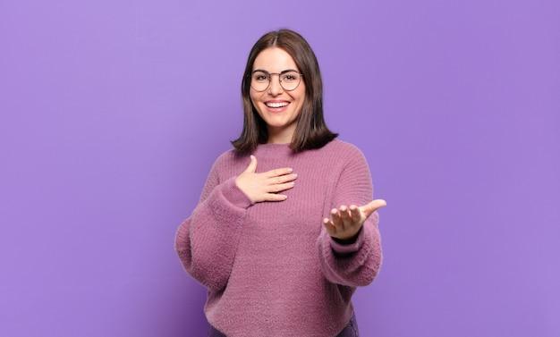 Jonge, vrij casual vrouw die zich gelukkig en verliefd voelt, glimlachend met de ene hand naast het hart en de andere vooraan gestrekt