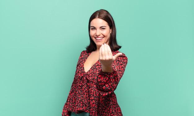 Jonge, vrij casual vrouw die zich gelukkig, succesvol en zelfverzekerd voelt, een uitdaging onder ogen ziet en zegt: kom maar op! of je verwelkomen