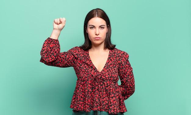 Jonge, vrij casual vrouw die zich serieus, sterk en rebels voelt, vuist opstekend, protesteert of vecht voor revolutie