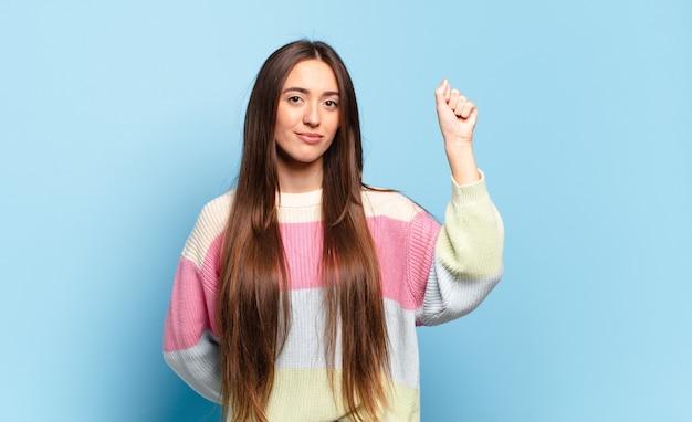 Jonge vrij casual vrouw die zich serieus, sterk en rebels voelt, vuist opstekend, protesteert of vecht voor revolutie