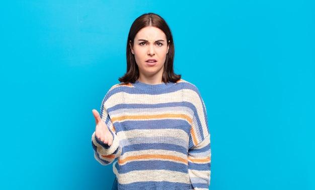 Jonge vrij casual vrouw kijkt boos, geïrriteerd en gefrustreerd schreeuwend wtf of wat is er mis met je