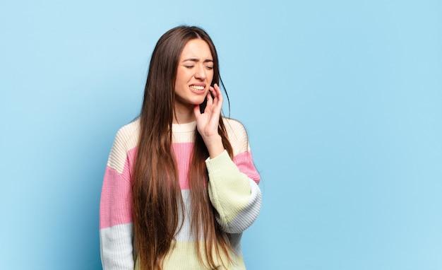Jonge vrij casual vrouw met wang en pijnlijke kiespijn, zich ziek, ellendig en ongelukkig voelen, op zoek naar een tandarts