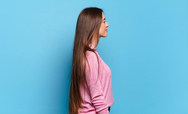 Jonge, vrij casual vrouw op profielweergave die ruimte vooruit wil kopiëren, denken, fantaseren of dagdromen