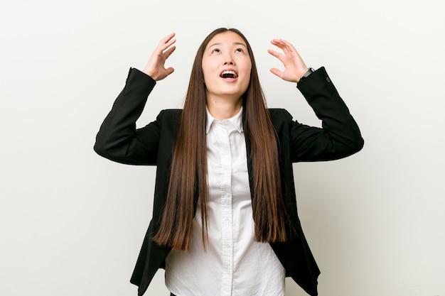 Jonge vrij chinese bedrijfsvrouw die aan de hemel gilt, gefrustreerd omhoog kijkt.