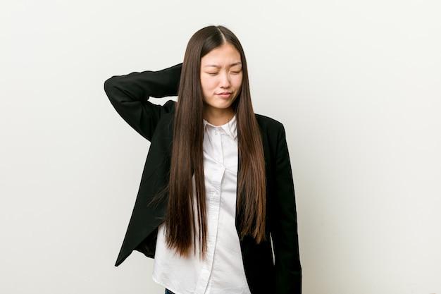 Jonge vrij chinese bedrijfsvrouw die aan nekpijn lijdt vanwege sedentaire levensstijl