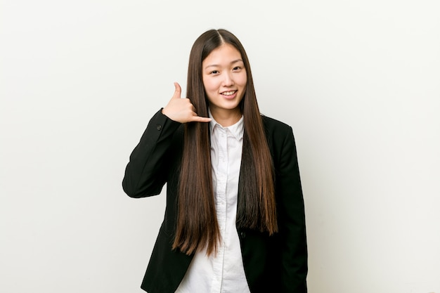 Jonge vrij chinese bedrijfsvrouw die een mobiel telefoongesprekgebaar met vingers toont.