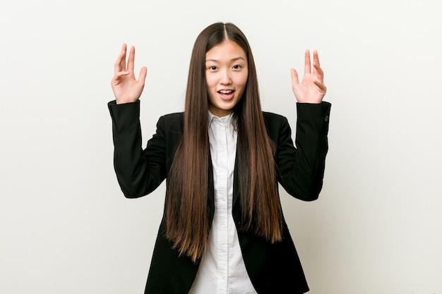 Jonge vrij chinese bedrijfsvrouw die een prettige verrassing ontvangt, opgewekte en handen opheft.