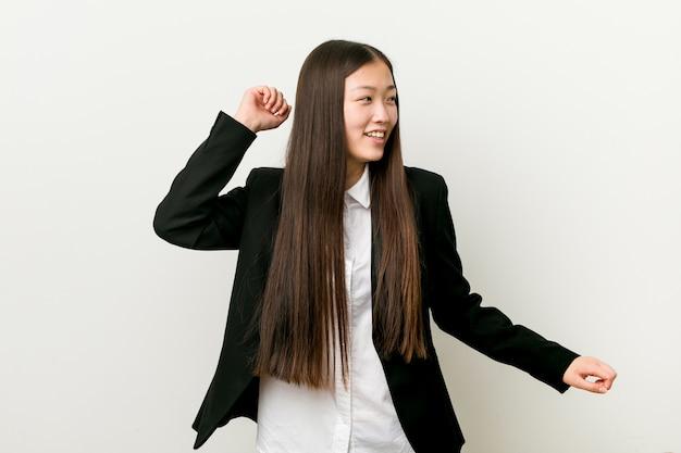 Jonge vrij chinese bedrijfsvrouw die en pret danst heeft.