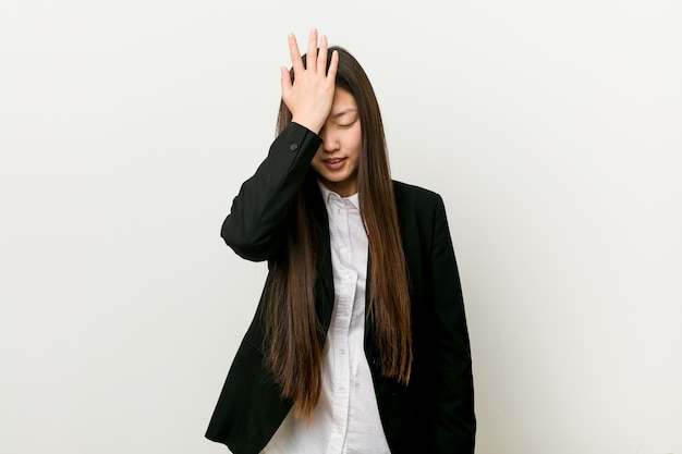 Jonge vrij chinese bedrijfsvrouw die iets vergeten, voorhoofd met palm meppen en ogen sluiten.