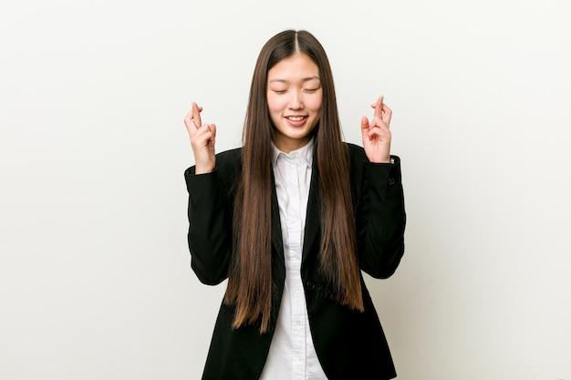 Jonge vrij chinese bedrijfsvrouw die vingers kruist voor het hebben van geluk