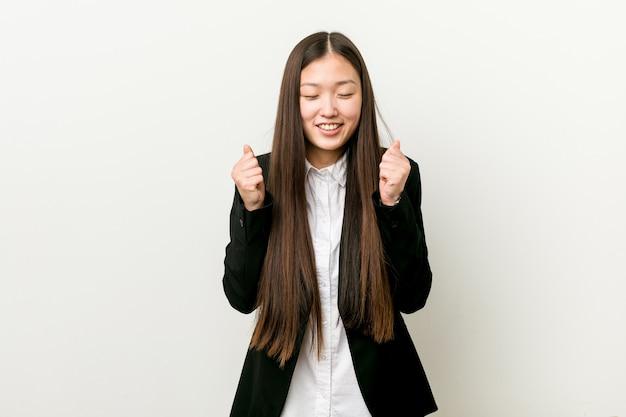 Jonge vrij chinese bedrijfsvrouw die vuist opheft, gelukkig en succesvol voelt. zege .