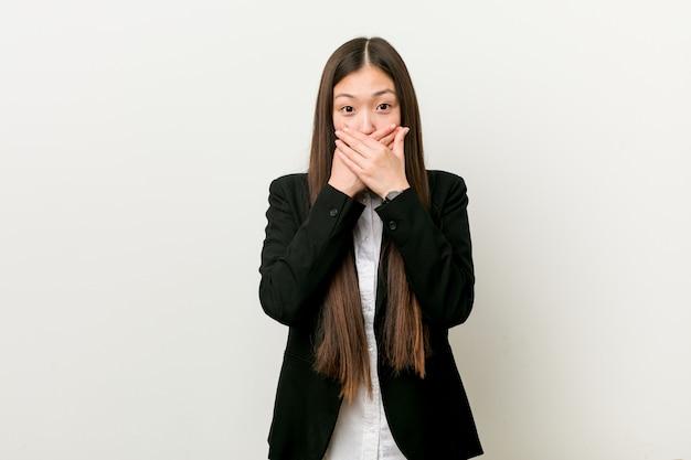 Jonge vrij chinese geschokte bedrijfsvrouw behandelend mond met handen.