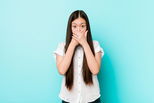 Jonge vrij chinese geschokte vrouw het behandelen van mond met handen.