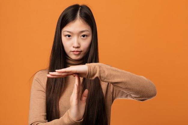 Jonge vrij chinese vrouw die een time-outgebaar toont.