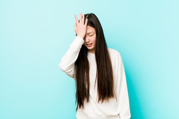 Jonge vrij chinese vrouw die iets vergeten, voorhoofd met palm meppen en ogen sluiten.