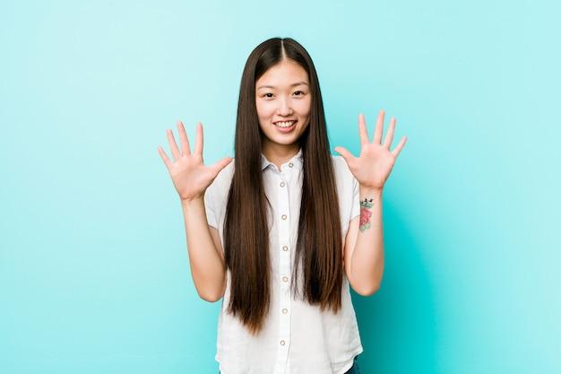 Jonge vrij chinese vrouw die nummer tien met handen toont.