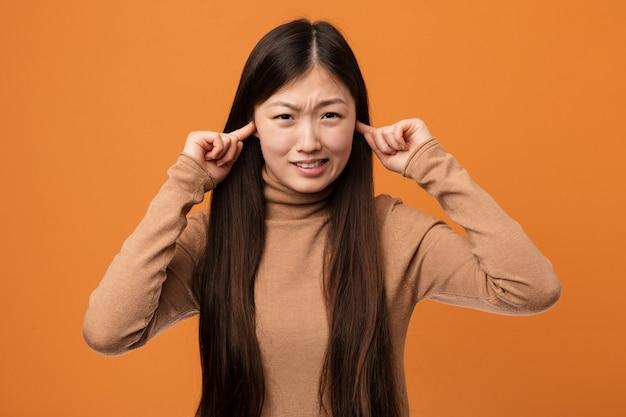 Jonge vrij chinese vrouw die oren behandelen met zijn handen.